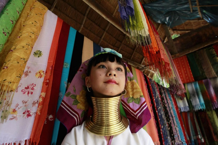 A long-neck Karen hill tribe girl prepares souvenirs as she waits for customers at her shop in Chiang Mai province, north of Bangkok. (Sukree Sukplang/Reuters)