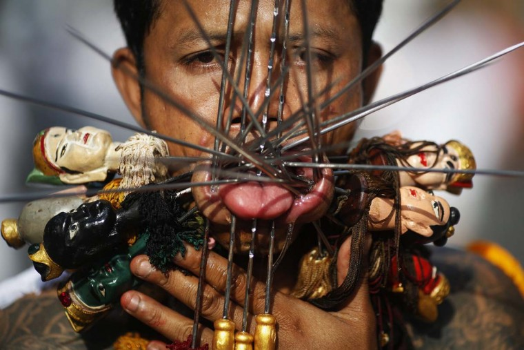 A devotee of the Chinese Kathu shrine with his face pierced takes part in a procession during the annual vegetarian festival in central Phuket October 22, 2012. The festival, featuring face-piercing, spirit mediums, and strict vegetarianism, celebrates the local Chinese community's belief that abstinence from meat and various stimulants during the ninth lunar month of the Chinese calendar will help them obtain good health and peace of mind. (Damir Sagolj/Reuters)