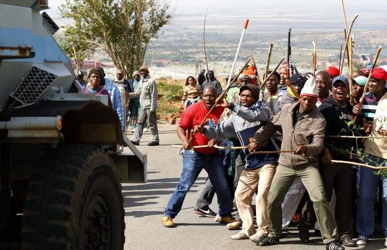 Striking miners react as they make way for a security vehicle at the AngloGold Ashanti mine in Carletonville, northwest of Johannesburg. AngloGold Ashanti sacked 12,000 wildcat strikers who defied a deadline to return to work on Wednesday, the latest South African company to resort to mass firings after weeks of crippling labour unrest. (Siphiwe Sibeko/Reuters)