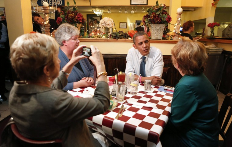 A woman takes a photo as U.S. President Barack Obama sits at their table at Antonellas Pizzeria in Davenport, Iowa. Obama is on a two-day, seven-state, campaign swing. (Kevin Lamarque/Reuters)