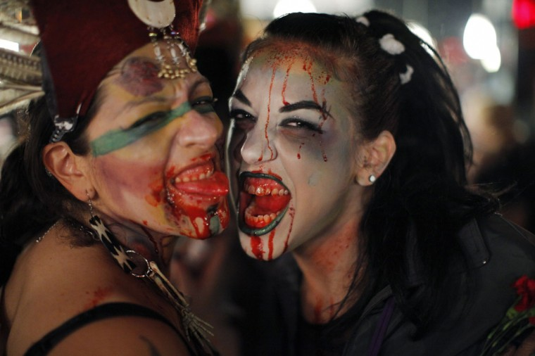 "Women dressed up as zombies pose for a picture during ""ZOMBIECON."" The event, held during Halloween celebrations, paid homage to the character typically depicted as the mindless walking dead with a penchant for human flesh and brains, made popular in movies, books and comics. (Eduardo Munoz/Reuters)"