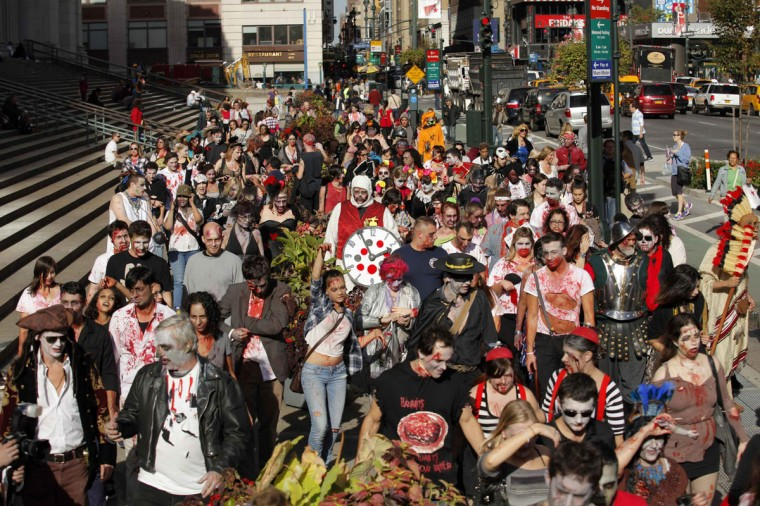 "People dressed up as zombies walk on a street during ""ZOMBIECON."" The event, held during Halloween celebrations, paid homage to the character typically depicted as the mindless walking dead with a penchant for human flesh and brains, made popular in movies, books and comics. (Eduardo Munoz/Reuters)"