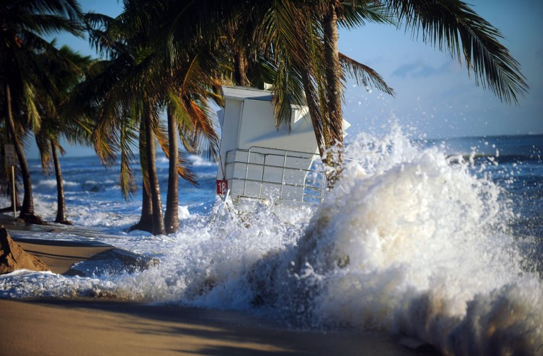 October 29, 2012: Waves crash over the seawall near a tilting lifeguard tower on A1A which is covered with sand from Hurricane Sandy, Monday at Ft. Lauderdale Beach. (Joe Cavaretta/SunSentinel)