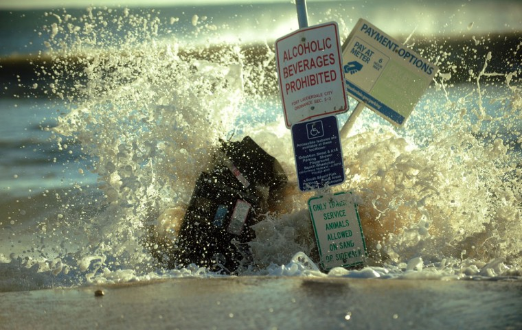 October 29, 2012: Waves crash over a parking meter machine and beach signage on A1A which is covered with sand from Hurricane Sandy, Monday at Ft. Lauderdale Beach. (Joe Cavaretta/SunSentinel)