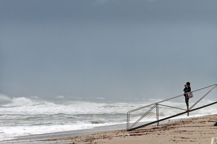 October 26, 2012: Melba Unsworth, of Bradenton, photographs the wicked weather on Ft. Lauderdale Beach on Friday as Hurricane Sandy passes to the east. Unsworth, who is here on vacation, said she 'likes to take pictures of things that wash up.' (Amy Beth Bennett/Sun Sentinel)