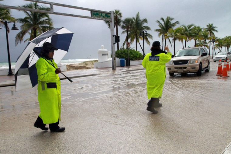 October 26, 2012: Ft. Lauderdale Police public safety aides Maggie Depasse, left, and Denise Melanson work traffic control on A1A at at SE 5th Street for the Ft. Lauderdale International Boat Show on Ft. Lauderdale Beach on Friday amid stormy, sandy conditions as Hurricane Sandy passes to the east. (Amy Beth Bennett/Sun Sentinel)