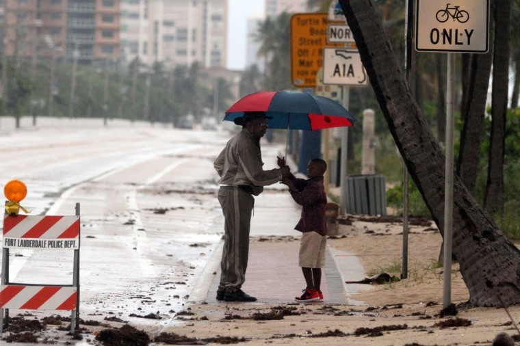October 26, 2012: Thaddeus Hamilton, of Sunrise, holds an umbrella for his grandson Christian Hamilton, 6, of Lauderhill, as they check out sand and debris onto the roadway on A1A between Sunrise Blvd. and NE 20th Street due to earlier flooding on Ft. Lauderdale Beach on Friday as Hurricane Sandy passes to the east. (Amy Beth Bennett/Sun Sentinel)