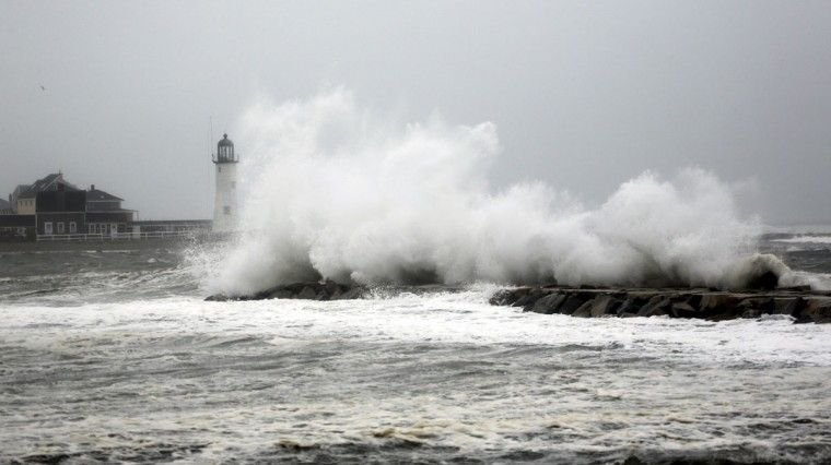October 29, 2012: Waves from Hurricane Sandy crash over the outer break wall of Scituate Harbor, Massachusetts with Scituate Light in the background an hour before high tide. (Greg M. Cooper/US Presswire)