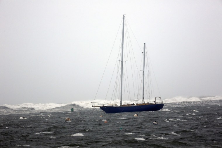October 29. 2012: A lone sailboat is moored in Scituate Harbor, Massachusetts as the waves from Hurricane Sandy crash against the outer break wall. (Greg M. Cooper/US Presswire)