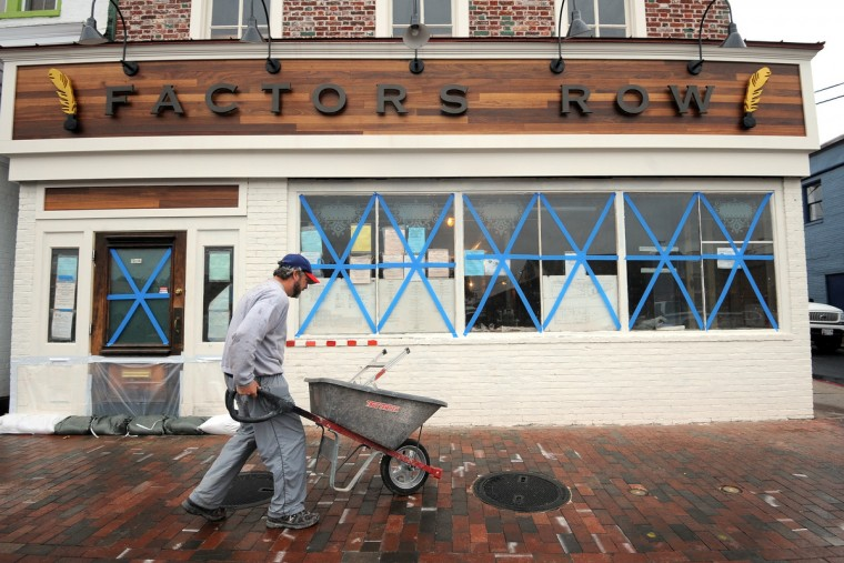 P.J. Mailloux, general manager of Factory Row, wheels away a step ladder he used to tape windows of the building. Annapolis merchants get ready for Hurricane Sandy. (Algerina Perna/Baltimore Sun)