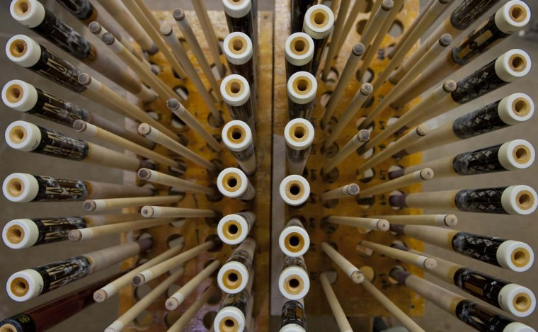 Nearly finished pool cues wait to be undercut for the special string, called Irish Linen wrap, at Joss Cues. (Karl Merton Ferron/Baltimore Sun)