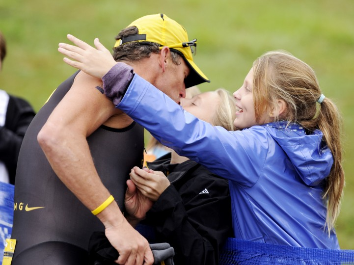 Lance Armstrong is embraced and kissed by his daughters, Grace, right, and Isabelle, center, as he begins the third leg of the Half Full Triathlon. (Jon Sham/BSMG)