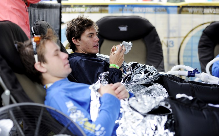 Ben Stout of Wilton, Conn., left, and Danny Gibney of Harrisonburg, Va., relax in leg compressors after finishing the triathlon. (Jon Sham/BSMG)