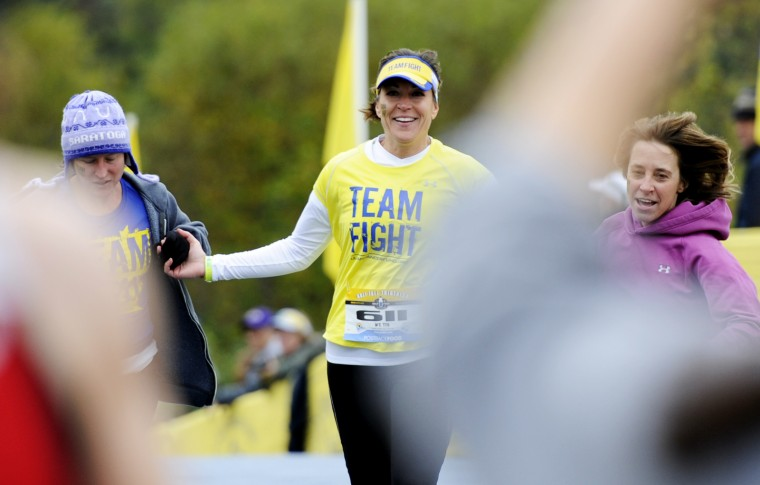 Judy Hanson of Ellicott City, center, makes her way to the finish line with friends Jamie Riordan of Arbutus, left, and Karen Kyger of Ellicott City. (Jon Sham/BSMG)