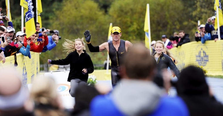 Lance Armstrong, with his daughters Grace, left, and Isabelle, right, is greeted by hundreds of cheering fans and cameras as he crosses the finish line. (Jon Sham/BSMG)
