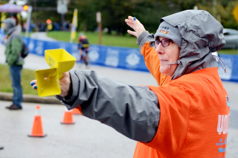 Lisa Goodman of Atlanta volunteered to be a bell-ringer at the triathlon, directing bikers and cheering them as they passed by. (Jon Sham/BSMG)