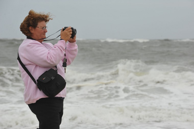 As the wind blows her hair Debbie Garrett of Easton takes photos of the huge waves in the inlet in Ocean City Saturday as hurricane Sandy gets closer to land. (Todd Dudek/Daily Times)