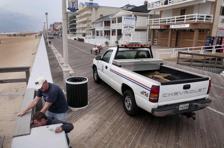 Ocean City Public Works employees Matt Mitchell, lower left, and Jamie Ellis, close the storm doors along the Boardwalk in Ocean City Saturday afternoon near 13th Street in preparation for Hurricane Sandy. (Grant L. Gursky/Daily Times)