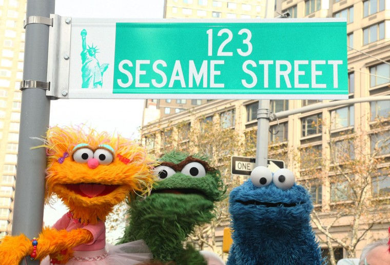 "Sesame Street characters pose under a ""123 Sesame Street"" sign in Dante Park in New York City. To honor the program's 40th anniversary, a street near the park was temporarily renamed. (Astrid Stawiarz/Getty Images)"