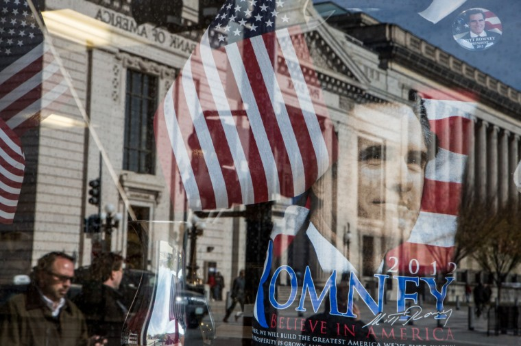 A street scene is reflected in the window of a gift shop near the White House on November 6, 2012 in Washington, DC. As Americans go to vote, recent polls show that President Barack Obama and Republican presidential candidate former Massachusetts Gov. Mitt Romney are in a virtual tie in the national polls. (Brendan Hoffman/Getty Images)