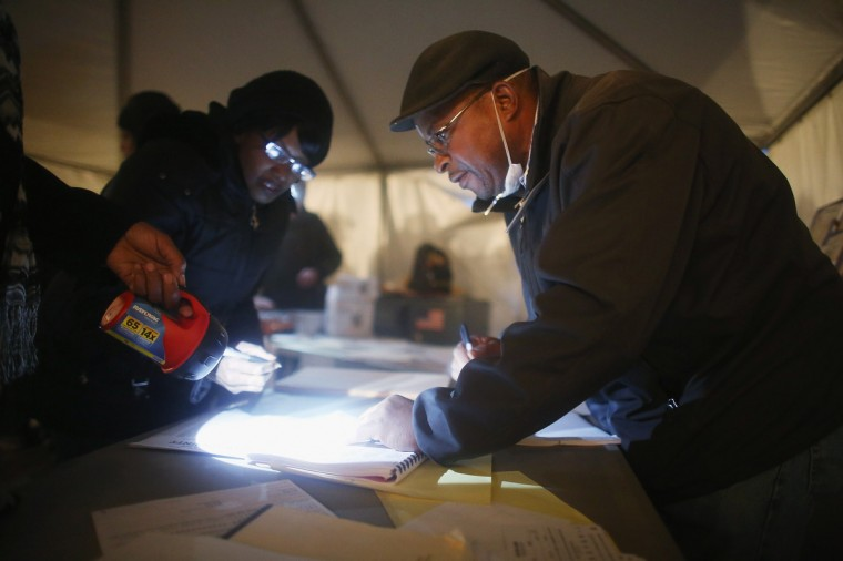 Poll worker Lloyd Edwards (R) assists voters with the help of a flashlight in a makeshift tent set up as a polling place at Scholars' Academy, PS 180, in the Rockaway neighborhood on November 6, 2012 in the Queens borough of New York City. The Rockaway section of Queens was one of the hardest hit areas. Many voters in New York and New Jersey are voting at alternate locations in the presidential election due to disruption from Superstorm Sandy. (Mario Tama/Getty Images)