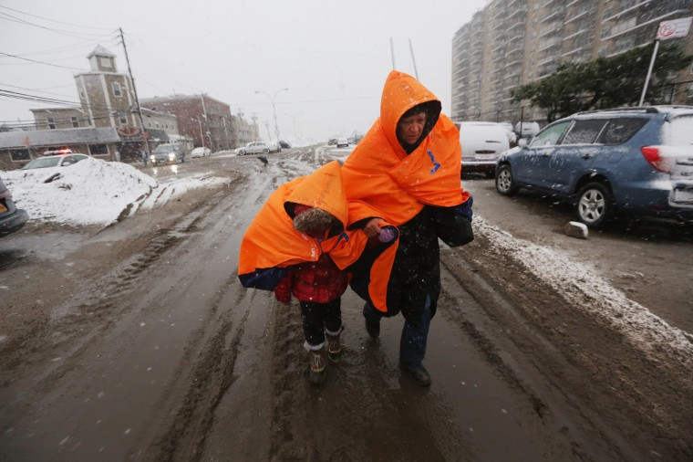 Fatima Quentiro walks with her granddaughter Galalea Castro through the snow to a bus stop to take a bus to Quenitro's home after Castro's home was damaged by flooding as a Nor'Easter approaches in the Rockaway neighborhood in the Queens borough of New York City. The two are wearing jackets donated by the NYC Marathon. The Rockaway Peninsula was especially hard hit by Superstorm Sandy and some are evacuating ahead of the coming storm. (Mario Tama/Getty Images)