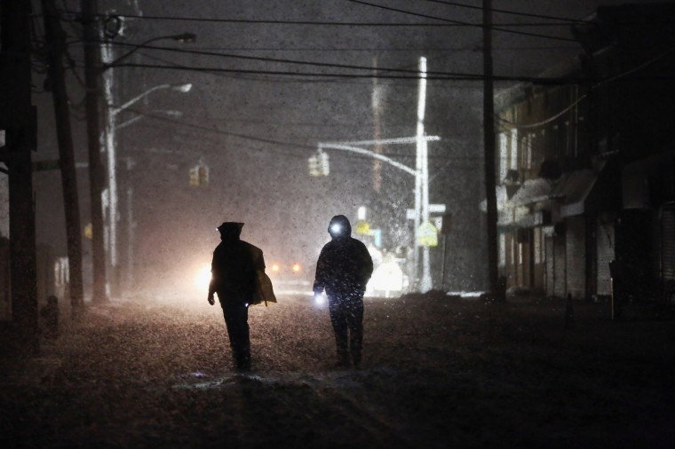 People walk through a darkened street using flashlights as a police spotlight shines behind them during a Nor'Easter snowstorm in the Rockaway neighborhood on November 7, 2012 in the Queens borough of New York City. The Rockaway Peninsula was especially hard hit by Superstorm Sandy and some are evacuating ahead of the coming storm. (Mario Tama/Getty Images)