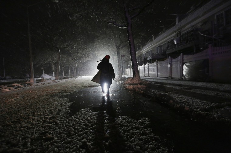 A repair worker is silhouetted by a police spotlight as he walks down a darkened street during a Nor'Easter snowstorm on November 7, 2012 in the Rockaway neighborhood of the Queens borough of New York City. (Mario Tama/Getty Images)