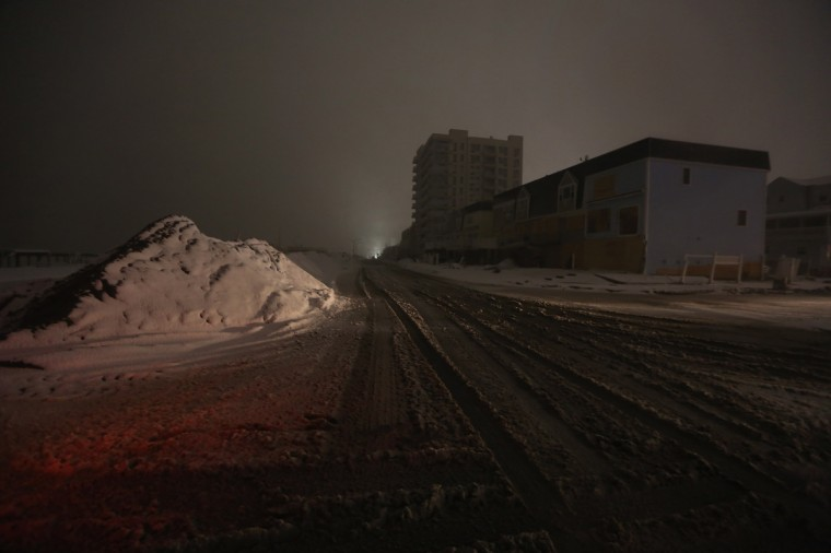 A darkened street is illuminated by police spotlights during a Nor'Easter snowstorm in the Rockaway neighborhood on November 7, 2012 in the Queens borough of New York City. The Rockaway Peninsula was especially hard hit by Superstorm Sandy and some are evacuating ahead of the coming storm. (Mario Tama/Getty Images)