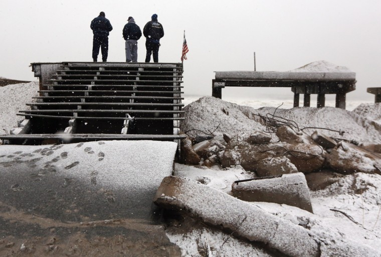 People stand on a destroyed section of boardwalk to check the storm's approach as a Nor'Easter arrives in the Rockaway neighborhood on November 7, 2012 in the Queens borough of New York City. The Rockaway Peninsula was especially hard hit by Superstorm Sandy and some are evacuating ahead of the coming storm. (Mario Tama/Getty Images)