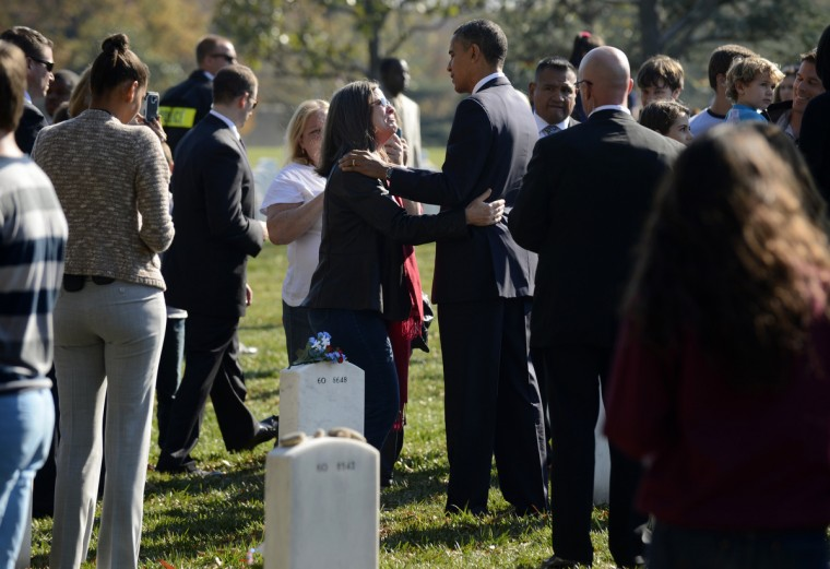 U.S. President Barack Obama (C) greets an unidentified woman on Veteran's Day at the Tomb of the Unknown Soldier in Arlington National Cemetery on November 11, 2012 in Arlington, Virginia. Section 60 is the final resting place for the majority of casualties Operation Iraqi Freedom in Iraq and Operation Enduring Freedom in Afghanistan. (Michael Reynolds/Getty Images)