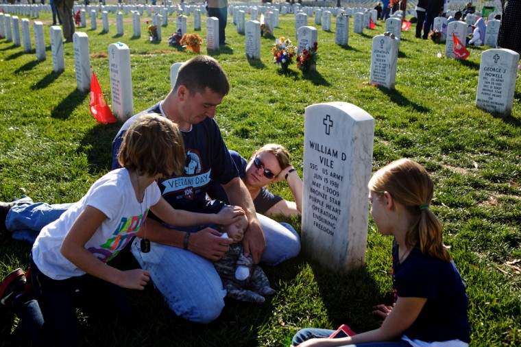 Jim Finnegan (L), his wife Carolyn and their children, Colleen, 7, Erin, 9, and William, 2 months, sit before the grave of Finnegan's best friend, Staff Sgt. William Vile who died in the war in Afghanistan in 2009, on Veteran's Day at Arlington National Cemetery on November 11, 2012 in Arlington, Virginia. Fiinnegan named his son after his friend who he had known since he was 14 years old. (Lexey Swall/Getty Images)