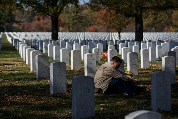 Capt. Jeff Cliffe, with the U.S. Marine Corps, sits next to the grave of his grandfather and grandmother on Veteran's Day at Arlington National Cemetery on November 11, 2012 in Arlington, Virginia. Numerous events are under across the country to honor the nation's current and former service members. (Lexey Swall/Getty Images)