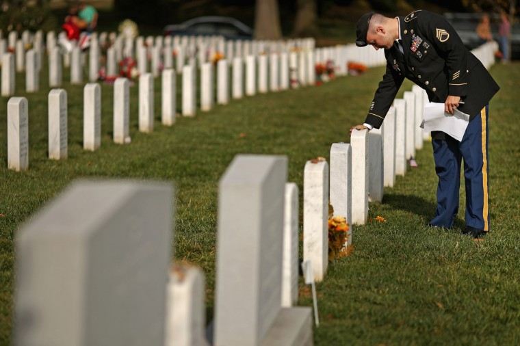 "The day after Veterans Day, U.S. Army Staff Sgt. Luke Parrott touches the headstone of a fellow soldier and friend in Section 60 at Arlington National Cemetery November 12, 2012 in Arlington, Virginia. A veteran of the wars in Afghanistan and Iraq, Parrott was injured in an IED blast in Baghdad in 2005. Parrott spent time sitting and talking to the graves of the soldiers he knew. ""It's as close as we can get to talking anymore,"" he said. (Chip Somodevilla/Getty Images)"