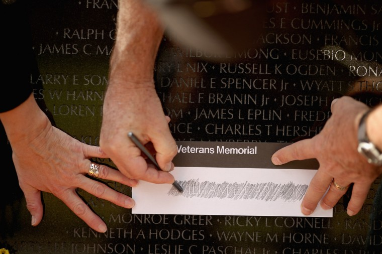 U.S. Army veteran James Clemenson of Vergas, Minnesota, and his wife Rosie make a rubbing from a name on the Vietnam Veterans Memorial the day after Veterans Day, November 12, 2012 in Washington, DC. From 1970 to 1972, James Clemenson did two tours during the Vietnam War and was the last enlisted Vietnam veteran in the U.S. Air Force after serving for 41 years, 4 months and two days, he said. (Chip Somodevilla/Getty Images)