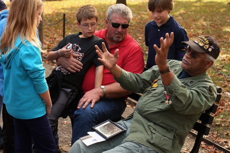Anna Tollette, 10; Nate Tollette, 12; and Brian Jon Raichert, 12; and their grandfather Bill Brandt (3rd L) of Antigo, Wisconsin, listen to Vietnam War veteran Charles Smith tell the story of how he earned the Bronze Star during the battle of Phan Thiet at the Vietnam Veterans Memorial the day after Veterans Day, November 12, 2012 in Washington, DC. Smith of Laurel, Maryland, served in the U.S. Army for 31 years and was awarded both the Bronze Star and the Purple Heart during this two tours of Vietnam. (Chip Somodevilla/Getty Images)