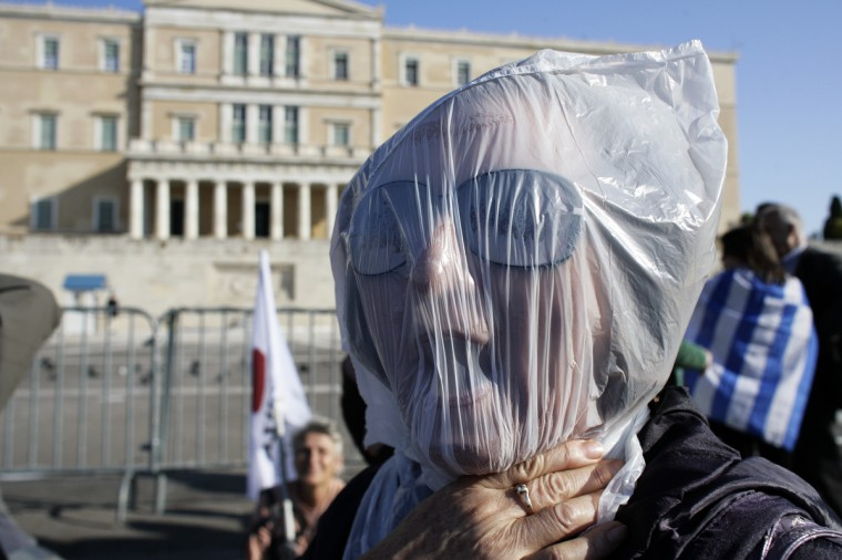 A protester wears a plastic bag on face during an anti-austerity protest in Athens, Greece. Unions in Spain, Portugal and Greece went on strike in what has become the first broad-based anti-austerity action to protest government plans amid a wide economic scope across Europe. (Photo by Milos Bicanski/Getty Images)
