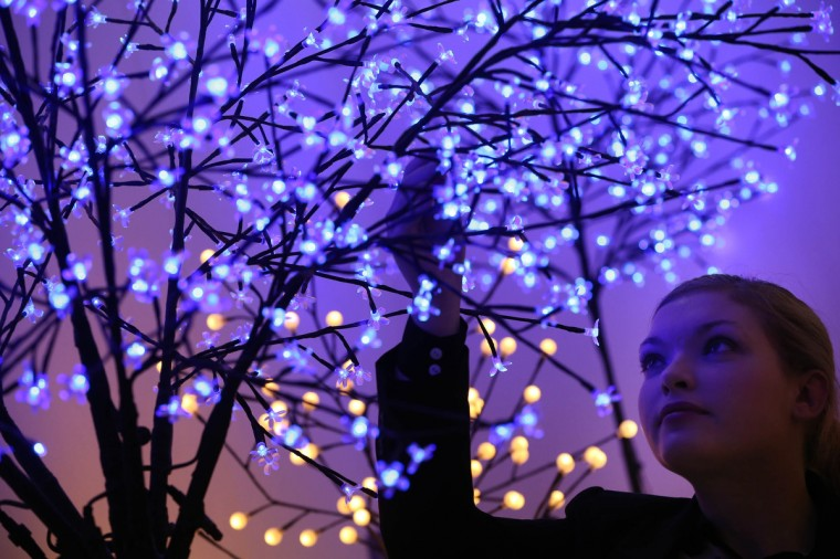 A sales assistant looks up at Christmas tree lights on display at The Ideal Home Christmas Show in London, England. Over 400 exhibitors are showcasing a range of gift ideas for Christmas at the Earls Court exhibition centre. (Peter Macdiarmid/Getty Images)