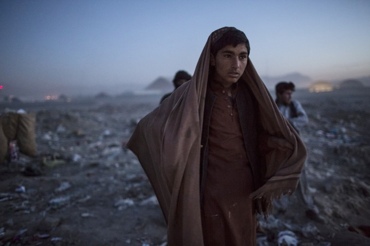 An Afghan Pashtun boy, who said he was forced from the troubled province of Baglan due to threats from the Taliban, looks on as he winds up for the day after scavenging for recyclables at a garbage dump site in Kabul, Afghanistan. Children working at the garbage site in Kabul said they can make up to 90 Afghans (USD $1.75) per day collecting cans and other recyclable materials for sale. If they were to stay and work in their home province, with limited options for employment, and join the Police or Army, the Taliban threatened they would come for them and their families, they said. (Daniel Berehulak/Getty Images)