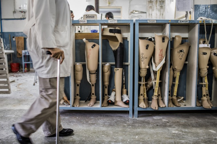 An orthopedic technician walks past prosthetic limbs being stored for patients at the International Committee of the Red Cross (ICRC), orthopedic centre in Kabul, Afghanistan. The ICRC rehabilitation centre works to educate and rehabilitate land-mine victims, and those with limb related deformities, back into society and employment offering micro-credit financing, home schooling and vocational training to patients. The clinic itself is unique in that all of the workers are handicapped. The ICRC centre in Kabul has registered over 57,000 patients and 114,000 countrywide in all of their centres since its inception 25 years ago. (Daniel Berehulak/Getty Images)