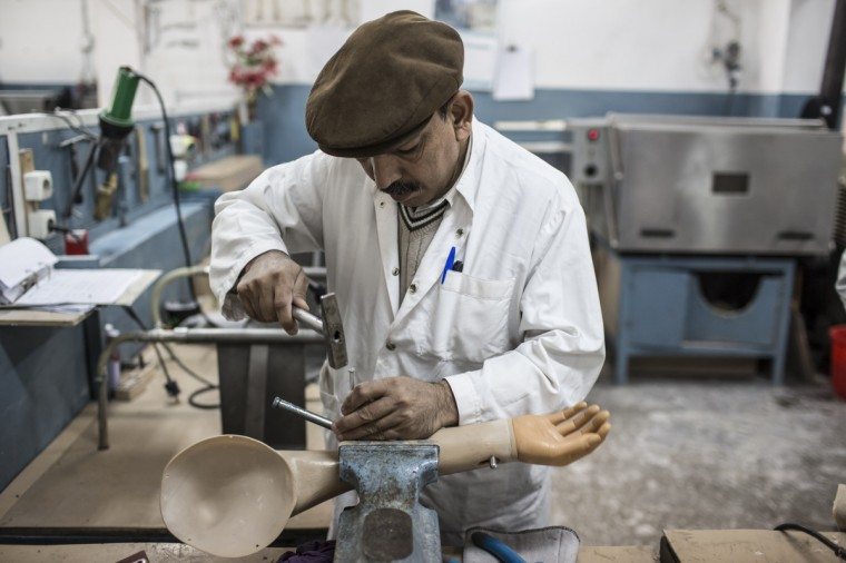 An orthopedic technician works on a prosthetic arm at the International Committee of the Red Cross (ICRC), orthopedic centre on November 20, 2012 in Kabul, Afghanistan. The ICRC rehabilitation centre works to educate and rehabilitate land-mine victims, and those with limb related deformities, back into society and employment offering micro-credit financing, home schooling and vocational training to patients. The clinic itself is unique in that all of the workers are handicapped. The ICRC centre in Kabul has registered over 57,000 patients and 114,000 countrywide in all of their centres since its inception 25 years ago. (Daniel Berehulak/Getty Images)