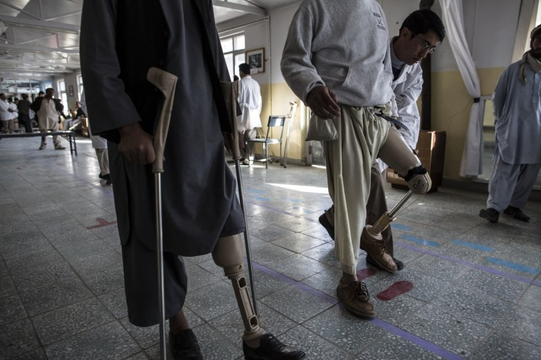 An orthopedic specialist checks the mobility of new prosthetic limb being fitted on to a patient at the International Committee of the Red Cross (ICRC), orthopedic centre in Kabul, Afghanistan. The ICRC rehabilitation centre works to educate and rehabilitate land-mine victims, and those with limb related deformities, back into society and employment offering micro-credit financing, home schooling and vocational training to patients. The clinic itself is unique in that all of the workers are handicapped. The ICRC centre in Kabul has registered over 57,000 patients and 114,000 countrywide in all of their centres since its inception 25 years ago. (Daniel Berehulak/Getty Images)