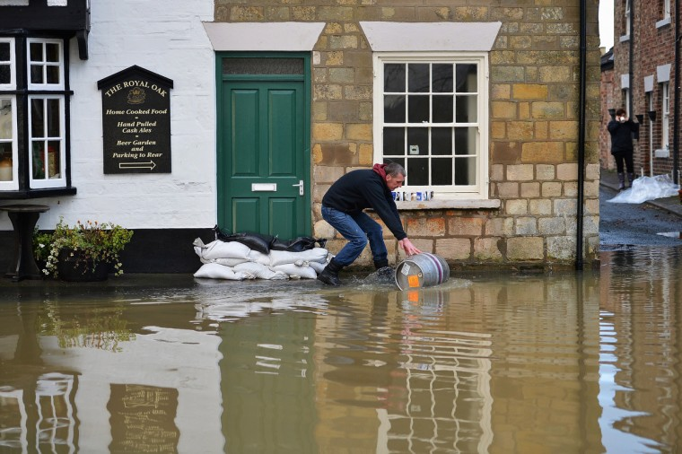 Residents of Old Malton begin to deal with the aftermath of the recent floods in Old Malton, England. Fire crews continue to pump large amount of surface flood water away from overflowing drains that have been threatening many properties in the area. (Jeff J Mitchell/Getty Images)