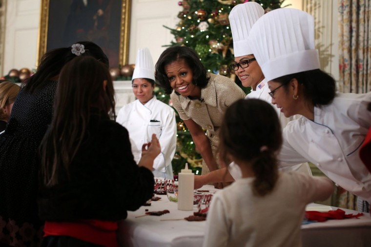 U.S. first lady Michelle Obama (C) participates in craft activities with military children at the State Dining Room after a preview of the 2012 White House holiday decorations in Washington, DC. The first lady welcomed military families, including Gold Star and Blue Star parents, spouses and children, to the White House for the first viewing of the 2012 holiday decorations. (Alex Wong/Getty Images)
