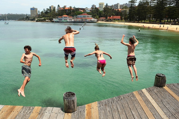 People dive off Manly Wharf in Sydney, Australia. Temperatures in the high 30s and low 40s celsius are expected to hit parts of the state over the weekend. (Brendon Thorne/Getty Images)
