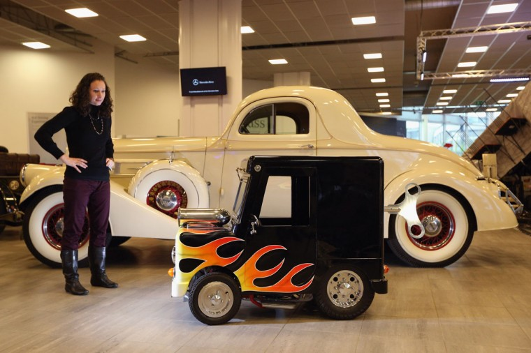 An employee of Bonhams auction house admires a Shanghai Shenke 'Wind Up', which is the world's smallest roadworthy car, and features in the 'Important Motor Carts and Automobilia' auction with an estimate of 7,000 GBP on December 3, 2012, in Mercedes-Benz World in Weybridge, England. The auction also includes a Bladerunner RIB 35 Powerboat which was driven by footballer David Beckham as it carried the Olympic flame to the Olympic Stadium in the opening ceremony of the London 2012 Olympic Games. (Oli Scarff/Getty Images)