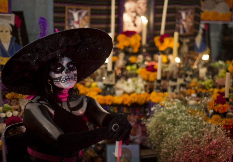 A woman in dressed up as the death poses with an Altar for the Dead in the background on October 31, 2012 in Mexico city, during preparations on the eve of the Day of the Dead celebrations. (Ronaldo Schemidt/AFP/Getty Images)