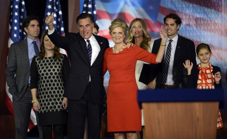 US Presidential candidate Mitt Romney and his wife Ann Romney wave to supporters as they are joined by their family on election night November 7, 2012 in Boston Massachusetts. Romney conceded the race to US President Barack Obama. Ann Romney is at left. (Timothy Clary/Getty Images)