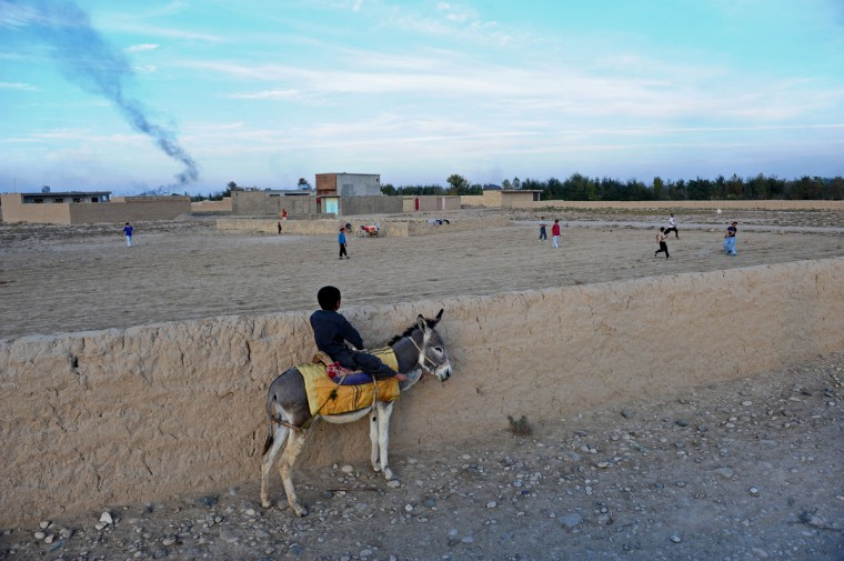 An Afghan boy sits on his donkey as he watches a football match in Dehdadi district of Balkh province. Over a third of Afghans are living in abject poverty, as those in power are more concerned about addressing their vested interests rather than the basic needs of the population, a UN report said. (Qais Usyan./Getty Images)