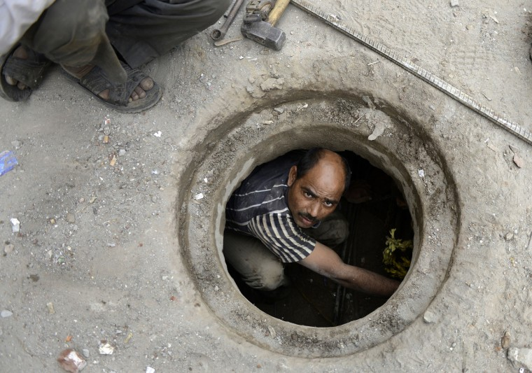 Indian plumber Jaipal looks up as he fixes an underground water pipe in New Delhi. Jaipal, an immigrant laborer who left his home in Jhansi in Uttar Pradesh state 13 years ago to work and settle in Delhi, earns INR 300 per day. Every year scores of poor workers come to Delhi in search of better employment opportunities. (Sajjad Hussain/Getty Images)